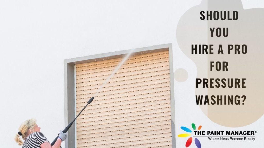 A woman pressure washing an exterior wall